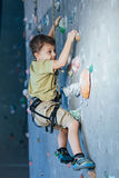 Little boy climbing a rock wall indoor. Concept of sport life Stock Images