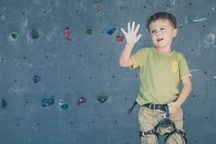 Little boy climbing a rock wall Stock Photography