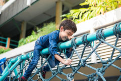 Little boy climbing on the rope at playground outdoor stock photos