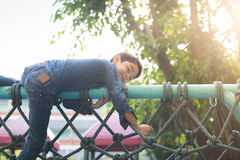 Little boy climbing on the rope at playground outdoor stock images