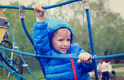 Little boy climbing rope on the playground Royalty Free Stock Photos