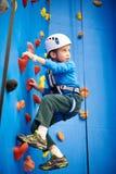 Little boy is climbing in sport park on blue wall. Little boy is climbing to amusement park on blue wall Stock Photo