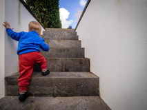 Little boy climbing steps. Cute baby boy climbing up the stairs stock images