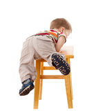 Little boy climbing on stool. Isolated on white Royalty Free Stock Image