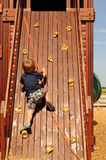 Little boy on climbing wall royalty free stock image