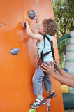Little boy climbing wall. Two years old child climbing on a wall in an outdoor climbing center. Child is supported by instructor Royalty Free Stock Photos