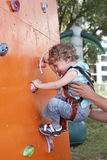 Little boy climbing wall. Two years old child climbing on a wall in an outdoor climbing center. Child is supported by instructor Royalty Free Stock Photo
