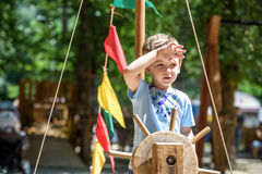 Little boy climbing on a wooden playground in rope park. Kid play outdoors warm sunny summer day Stock Image