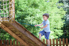 Little boy climbing on a wooden playground in rope park. Kid play outdoors warm sunny summer day Stock Images