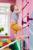 The little boy climbs up a wooden plate in the gym. The little kid climbs up a wooden plate in the gym Royalty Free Stock Photos