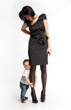 Little boy clinging to mother's leg stock images