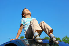 Little boy with closed eyes sitting on car roof Stock Photos