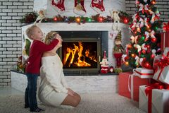 A little boy closed his mother`s eyes, surprise. Christmas presents under the tree.Merry Christmas and Happy Holidays!. Merry Christmas and Happy Holidays!A stock photos
