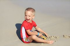 A little boy in clothes with UV filter is playing with sand on the beach by the sea, holiday with children, protecting kids from. A little boy in clothes with UV royalty free stock photography