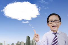 Little boy with a cloud bubble. Close up of cute boy wearing school uniform while thinking an idea and pointing at a cloud bubble in the sky Stock Photos