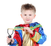 Little boy in clown costume holds slingshot and looks at camera Stock Image