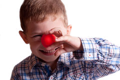 A little boy with a clown nose. On a white background Royalty Free Stock Photos
