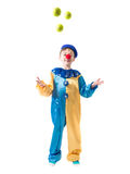 Little boy in clown suit juggling three balls and smiling. On a white background Royalty Free Stock Image