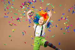 Little boy in clown wig jumping and having fun celebrating birth. Day. Portrait of a child throws up a multi-colored tinsel and confetti. Birthday boy. Positive Royalty Free Stock Images