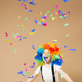 Little boy in clown wig jumping and having fun celebrating birth. Day. Portrait of a child throws up a multi-colored tinsel and confetti. Birthday boy. Positive Royalty Free Stock Photography