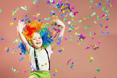 Little boy in clown wig jumping and having fun celebrating birth. Day. Portrait of a child throws up a multi-colored tinsel and confetti. Birthday boy. Positive Stock Photography