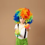 Little boy in clown wig playing with a spring. Royalty Free Stock Photography