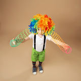 Little boy in clown wig playing with a spring Royalty Free Stock Photos