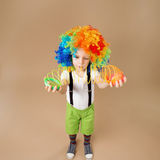 Little boy in clown wig plays with a spring. Royalty Free Stock Photography