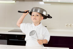 Little boy clowning around with kitchen utensils. Little boy in a white apron clowning around with kitchen utensils standing with a saucepan upended on his head stock photo