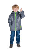 Little boy in a coat holds his thumb up Stock Images