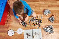 Little boy collects children's plastic building kit Stock Photos