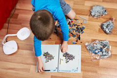 Little boy collects children's plastic building kit Stock Photography