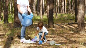 A little boy collects garbage in the woods and puts it in a bag with his mother. Family activists cares about nature