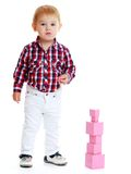 Little boy collects pink pyramid Royalty Free Stock Photo