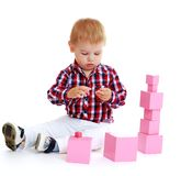 Little boy collects pink pyramid. Stock Image