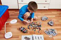 Little boy collects plastic constructor Royalty Free Stock Image