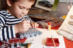 Little boy collects plastic model tank Royalty Free Stock Image