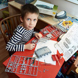 Little boy collects plastic model tank Stock Images