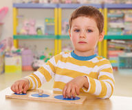 Little boy collects a puzzle Stock Images