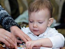 Little boy collects puzzles. With mum Stock Photography