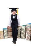 Little boy in collegiate cap with old books Stock Image