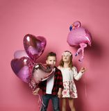 Little boy with color heart balloons and little girl with flamingo balloon are the birthday party or other holiday. On pink background stock images