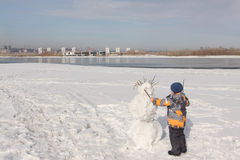 The little boy in a color jacket building a snowman Stock Images