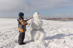 The little boy in a color jacket building a snowman Royalty Free Stock Image