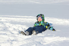 The little boy in a color jacket with a smile lying on snow Stock Photos