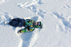 The little boy in a color jacket  with a smile lying  on snow Royalty Free Stock Images