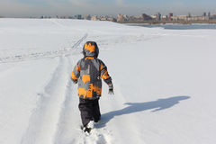 The little boy in a color jacket walking on the snow Royalty Free Stock Images