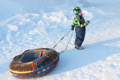 The little boy in color overalls  holding in hand  snow tubing Stock Photos