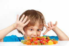 Little boy with colored jelly candies on white background Royalty Free Stock Photography