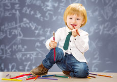 Little boy with colored pencil with blackboard Stock Image